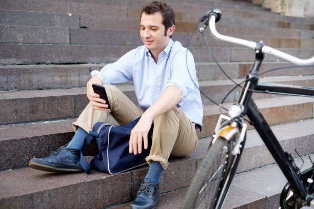 Man is resting next to his bike and using phone - foto stock