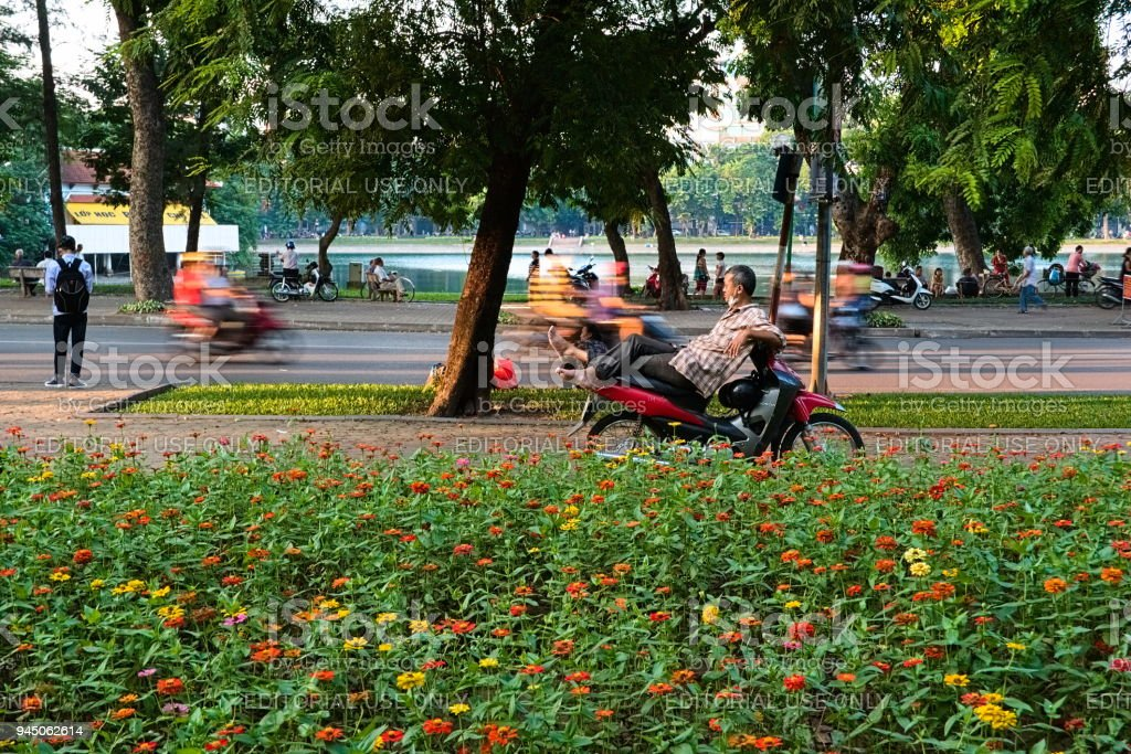 Man is resting on motorcycle on the street in Hanoi stock photo