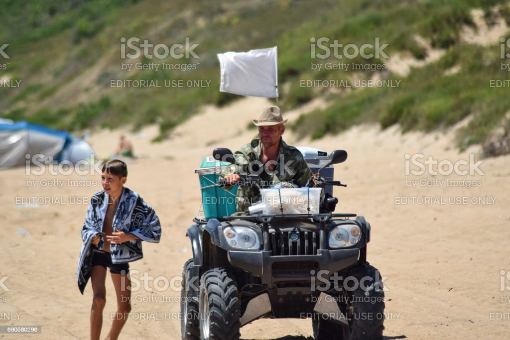 A man is riding a quad bike along the sandy beach of the sea. stock photo