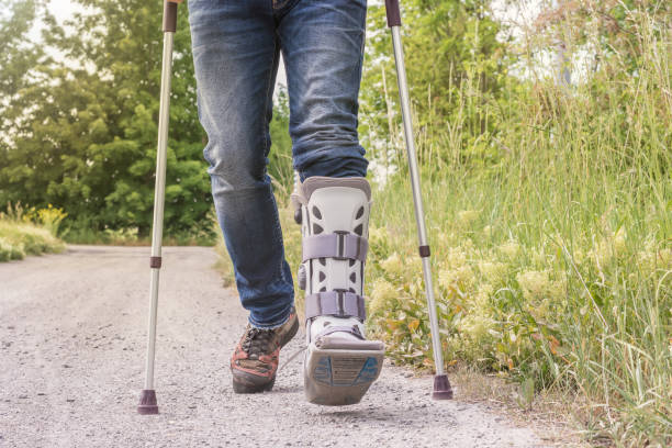 Man läuft mit einer Orthese und Gehhilfen auf einem Feldweg – Foto