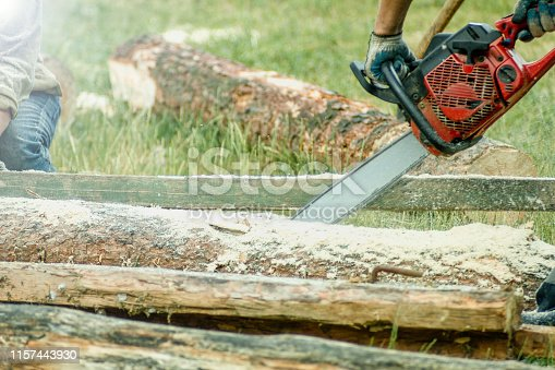 man is sawing a log with a chainsaw, carpentry.