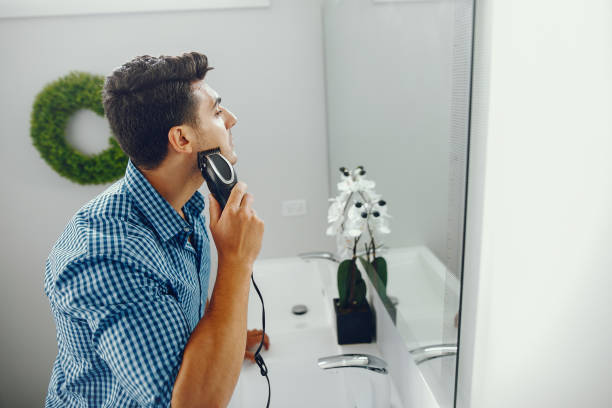 man is shaving his face stock photo