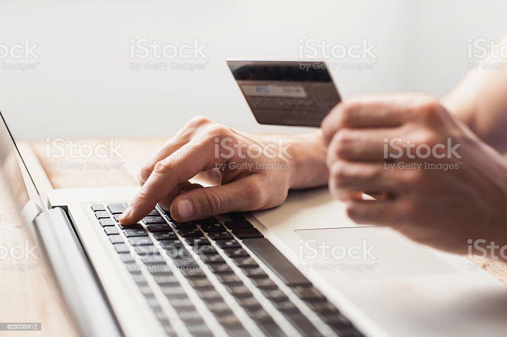 Hombre es de compras en línea con capacidad para computadora portátil - foto de stock