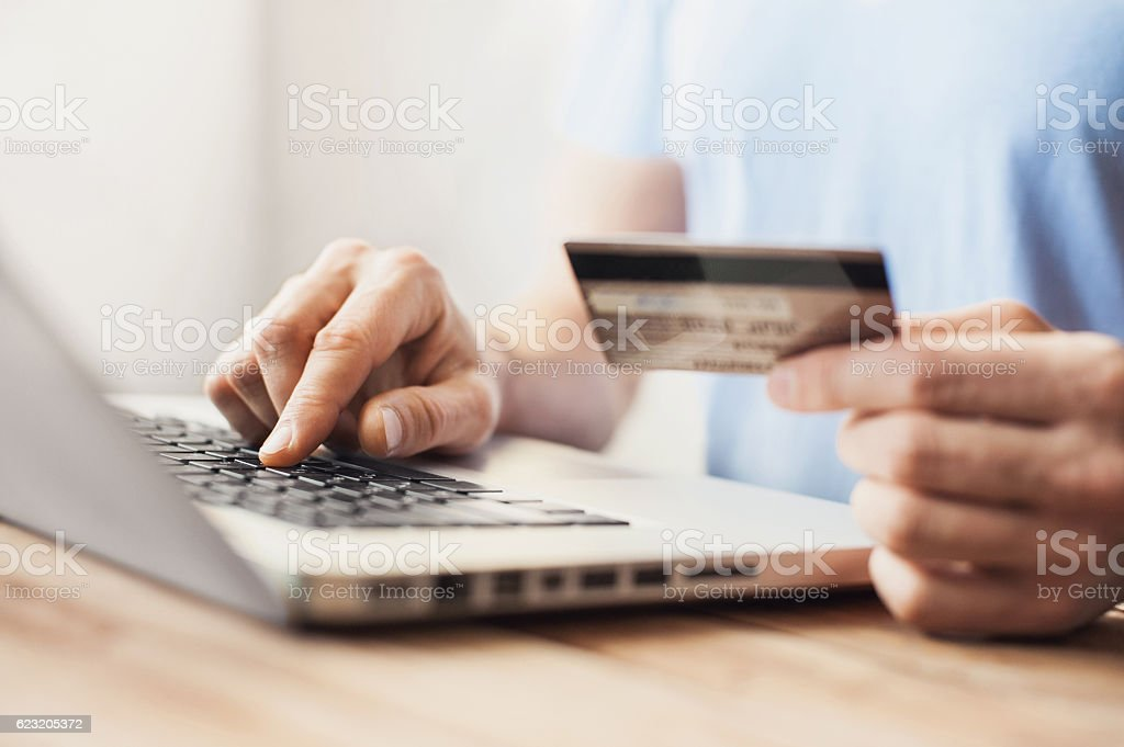 Man is shopping online with laptop Young man shopping with credit card and laptop computer Adult Stock Photo
