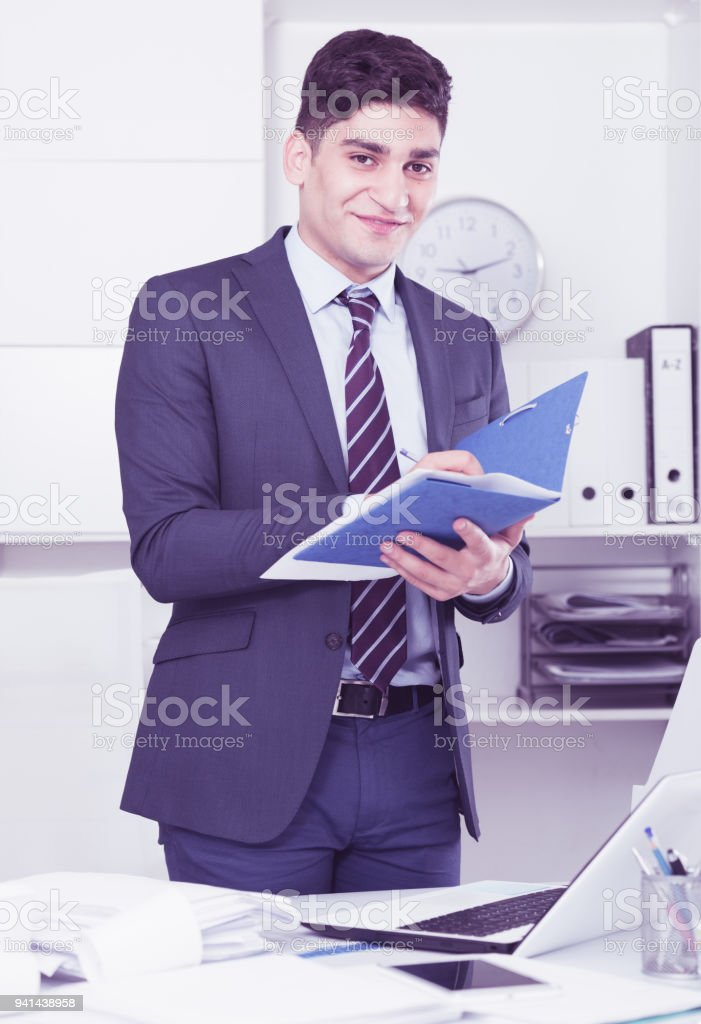 man is signing agreement papers of financial nature stock photo