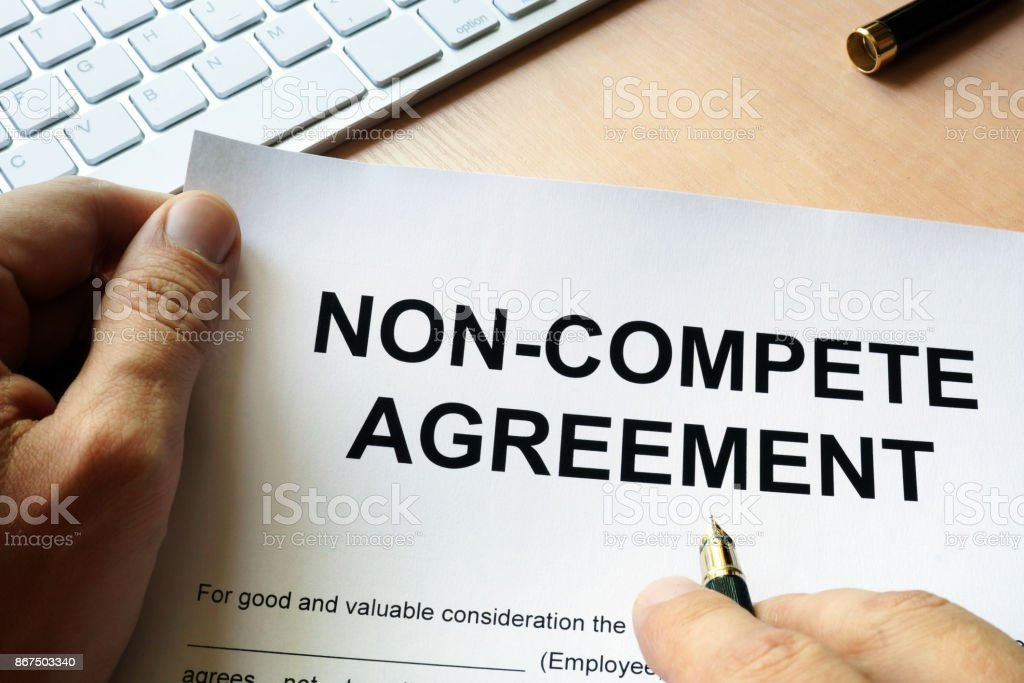 Man is signing Non compete agreement stock photo