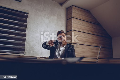 A man is sitting at the desk at the office