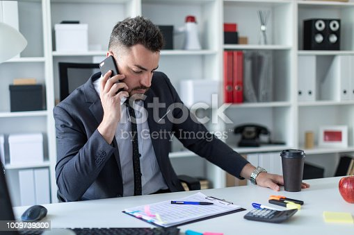 istock A man is sitting at the desk at the office, talking on the phone and holding a glass of coffee. 1009739300