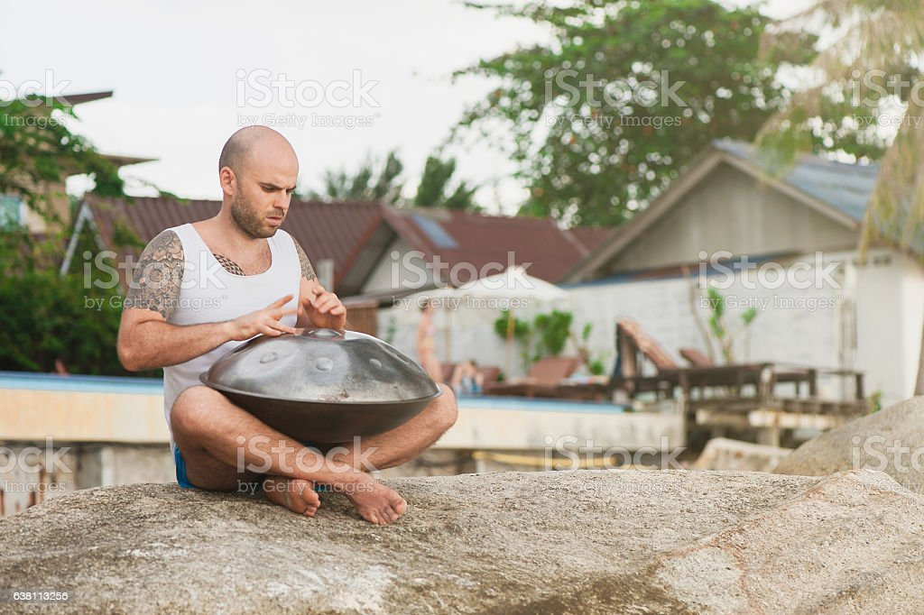 Man is sitting on the stone and playing hangdrum stock photo