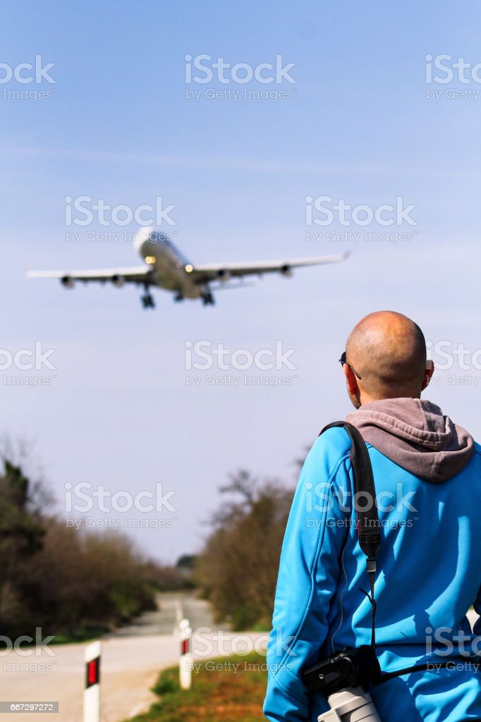 Man is spotting airplane. Spotting Airplane. Man is looking at the plane which is landing. Aircraft spotting concept. stock photo