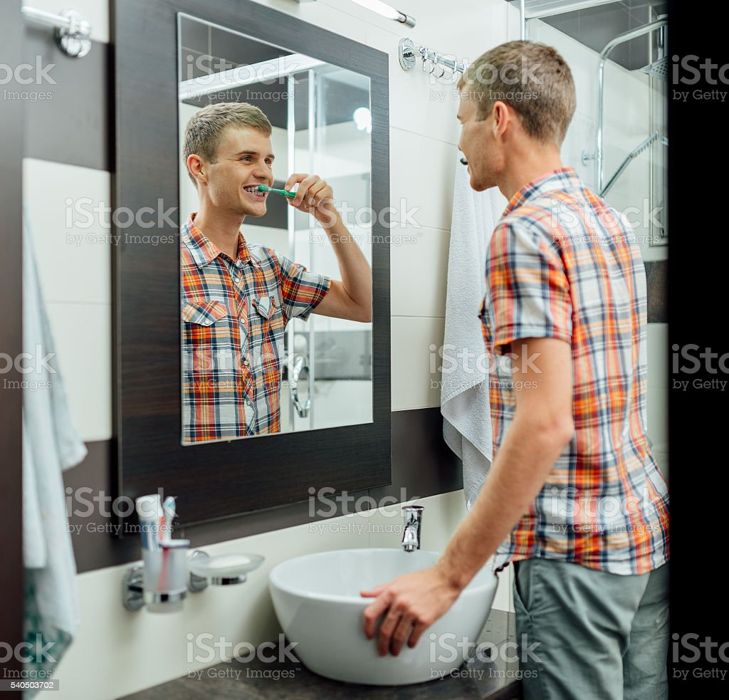 man is standing and cleaning his  teeth stock photo