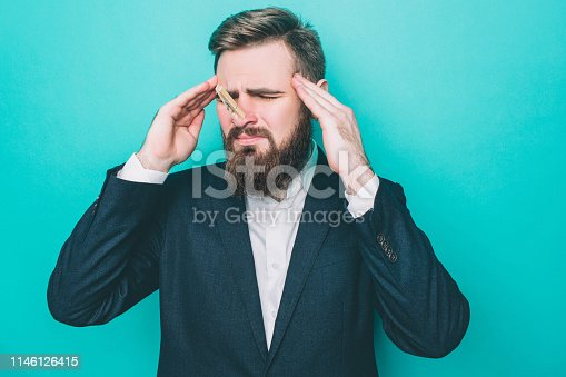 Man is standing and holding his hands close to head. He has a headache. Also guy's nose is closed with a clothespin. He can't breath very well. Isolated on blue background