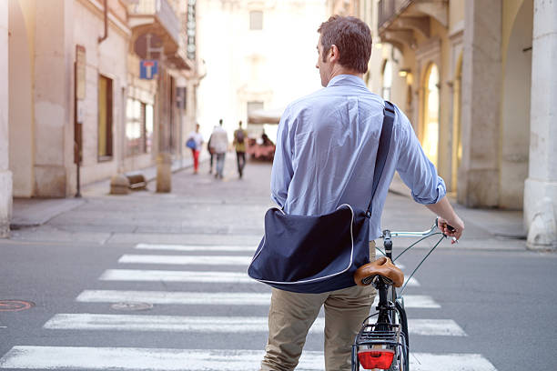 Man is standing crossing the city street with his bike - foto stock