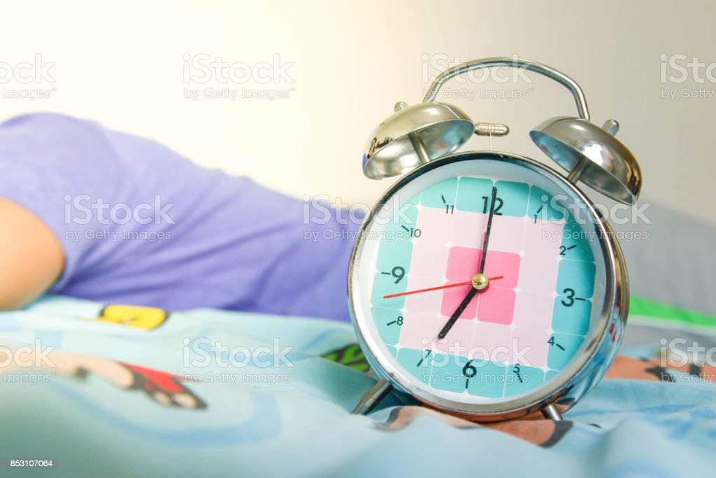 Man is still sleeping on the bed with Alarm clock is showing time for 7 AM stock photo