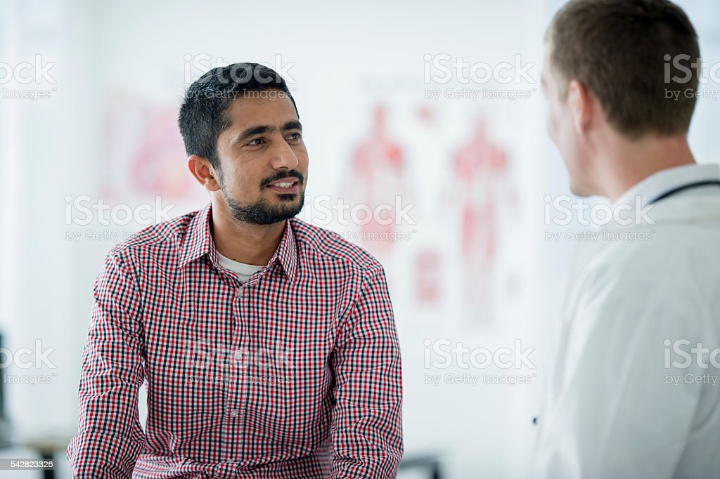 A man is talking with his doctor at an appointment. stock photo