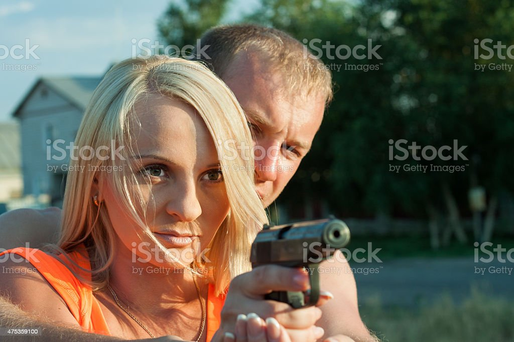 Man is teaching his girlfriend to shoot. stock photo