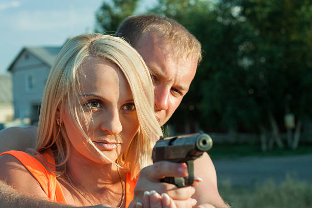 Man is teaching his girlfriend to shoot. stock photo