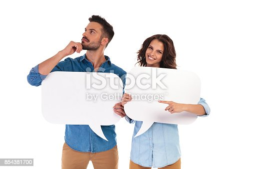 854381780istockphoto man is thinking while holding speech bubble near woman pointing 854381700
