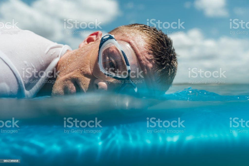 man is tired and lie on surfboard in the ocean stock photo