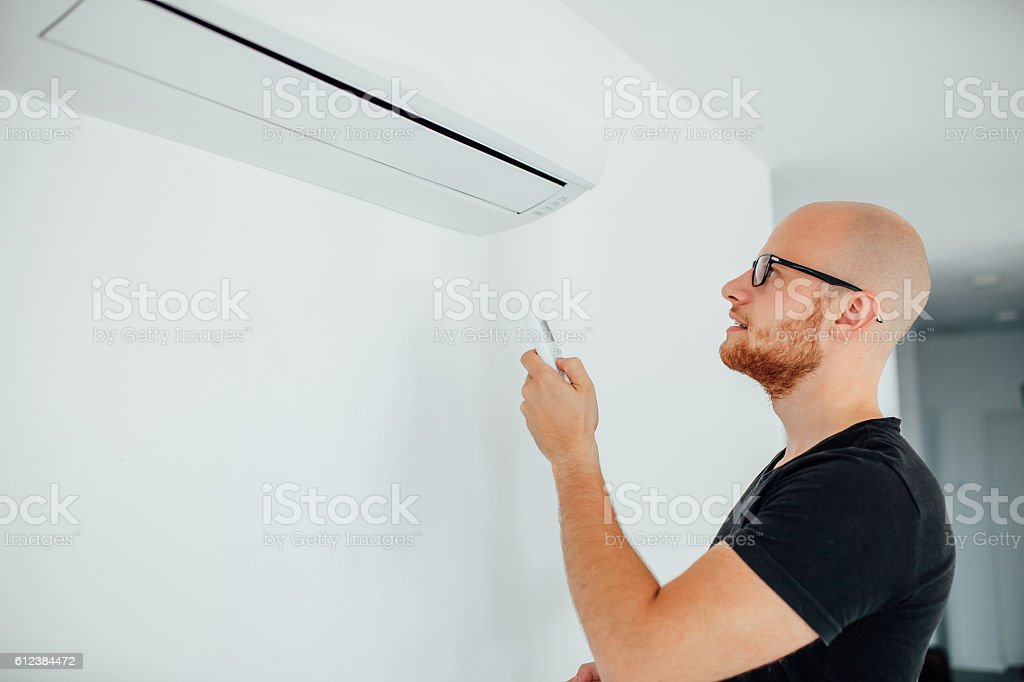 Man is turning on air condition by remote control. stock photo