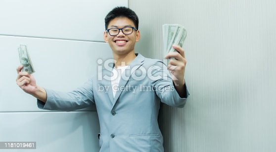 969671638istockphoto A man is very happy to hold banknotes in his hand 1181019461