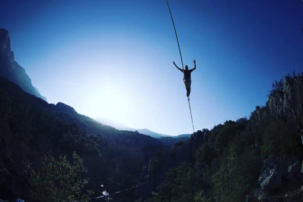 ein mann läuft entlang einer gestreckten schlinge. highline in den bergen. der mensch fängt das gleichgewicht. leistung eines seilwanderers in der natur. highliner auf dem hintergrund der berge. - gleichgewicht stock-fotos und bilder
