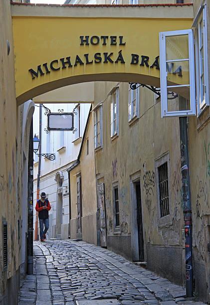 man is walking by the narrow street in bratislava, slovakia - bratislava hotel stock-fotos und bilder