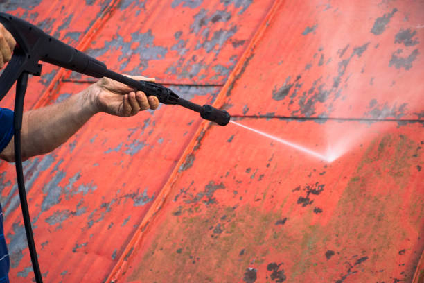 man is washing the roof with a high pressure washer - high pressure cleaning stock photos and pictures