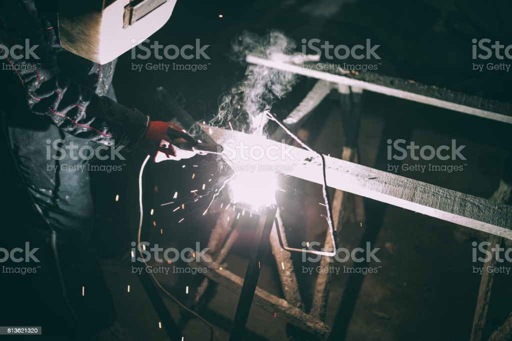 One man, doing his welding work alone.