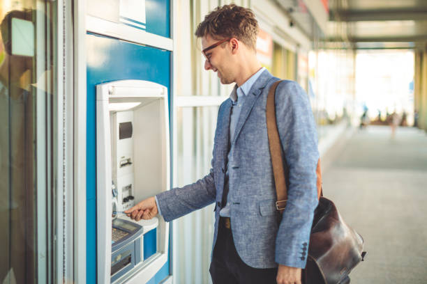 man is withdrawing cash from an atm machine - банки и банкоматы стоковые фото и изображения