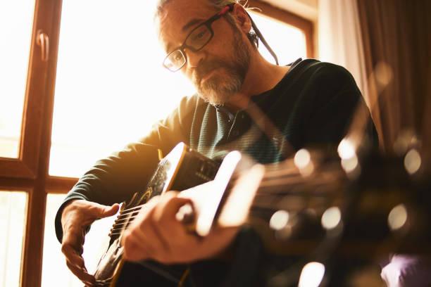 Ein Mann arbeitet zu Hause mit Gitarrenübungen – Foto
