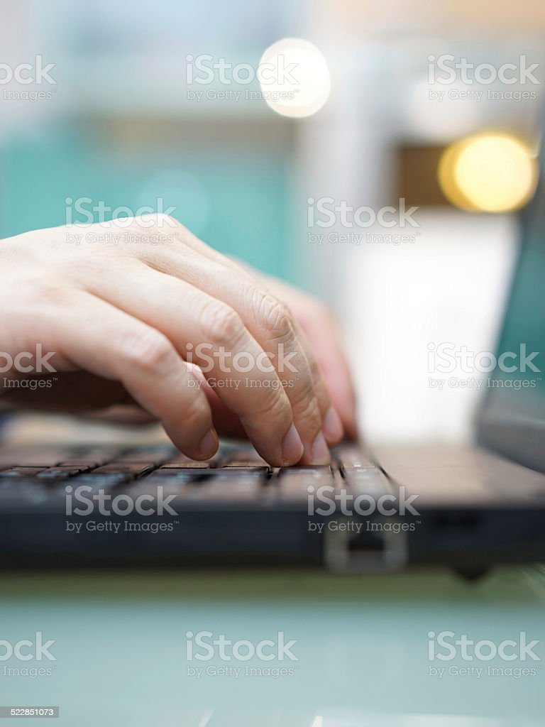 Man is working on laptop at home. Shallow depth field stock photo
