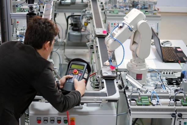 el hombre está trabajando para controlar un brazo robótico - robótica fotografías e imágenes de stock