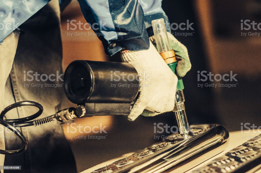 Man is working with a pneumatic rivet gun. Toned image. stock photo