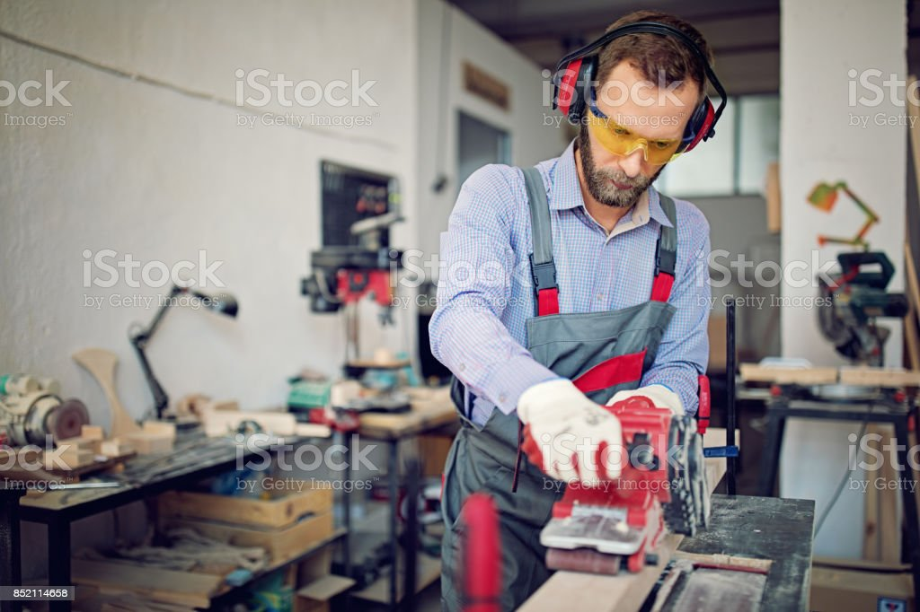Man is working with sander in small family carpenter factory stock photo