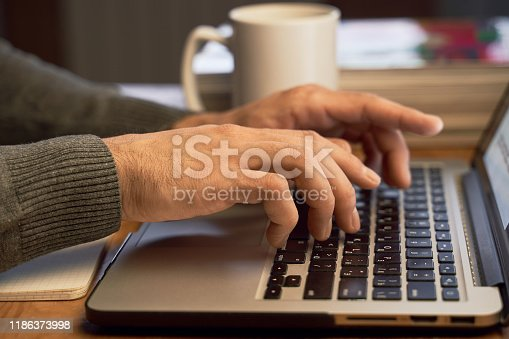 879813798istockphoto Man is writing a text on laptop and going to drink tea. 1186373998
