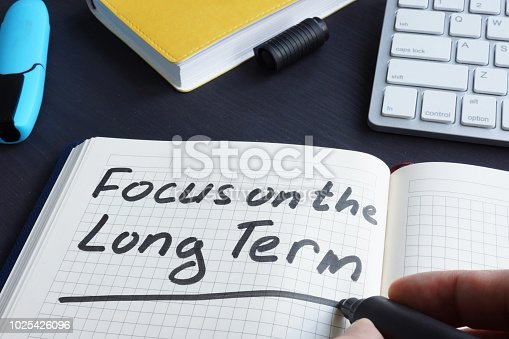 Man is writing focus on the long term.