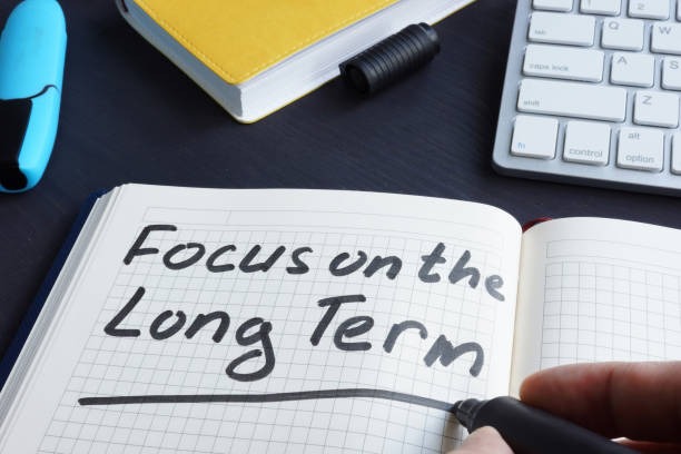 man is writing focus on the long term. - long stock pictures, royalty-free photos & images