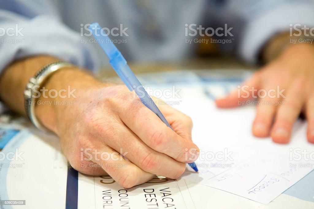 Homem está escrevendo informações para uma apresentação de timeshare (tempo compartilhado) foto royalty-free