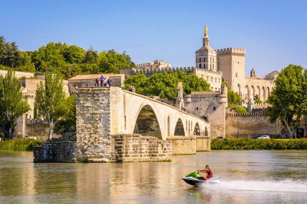 Un jet ski d'homme devant le pont d'Avignon et le palais papal à Avignon, France. - Photo