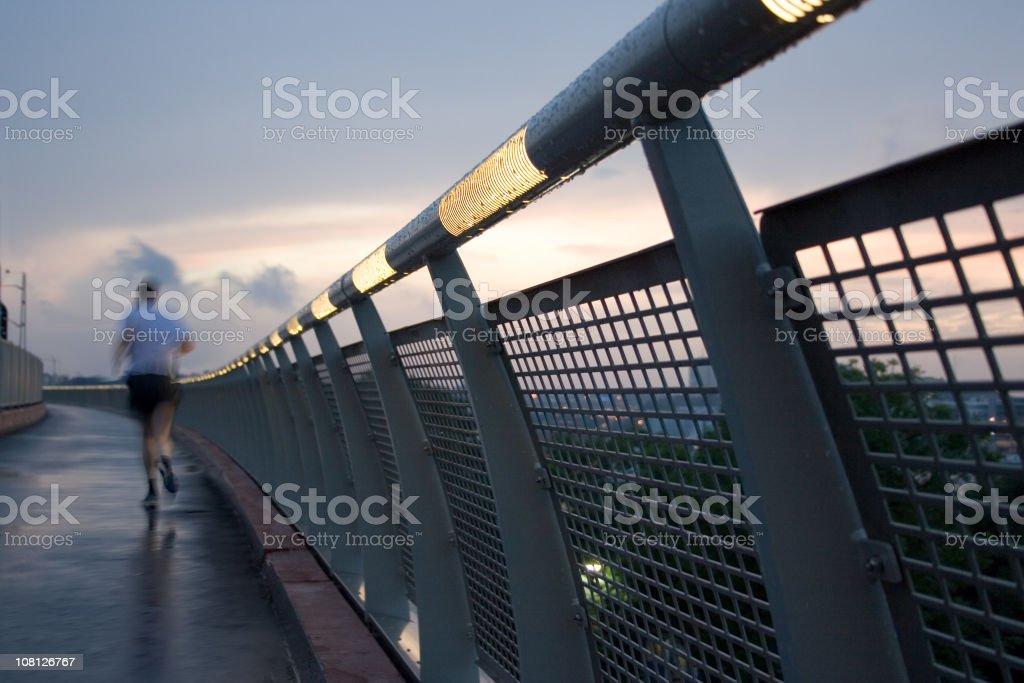 Man Jogging Along Bridge at Sunset royalty-free stock photo