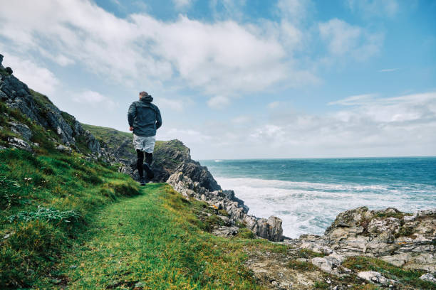 man jogging along the coastal rugged footpath at the cornish coast, newquay on a bright sunny autumn day. - cornwall stock pictures, royalty-free photos & images
