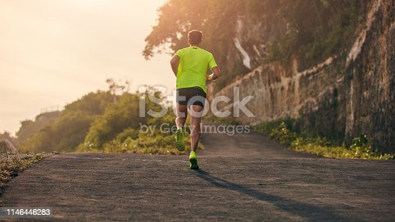 Man jogging on a downhill / uphill in suburb mountain road.