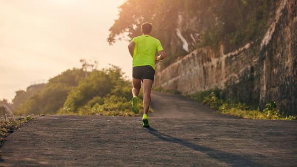 Man joggt auf einer Abfahrt/bergauf in Vorstadtbergstraße – Foto