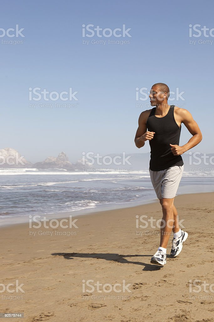 Man jogging on beach-vertical royalty-free stock photo