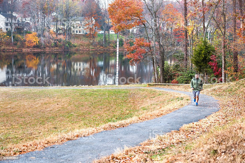 Man jogging on trail path by lake Woodglen in Virginia stock photo