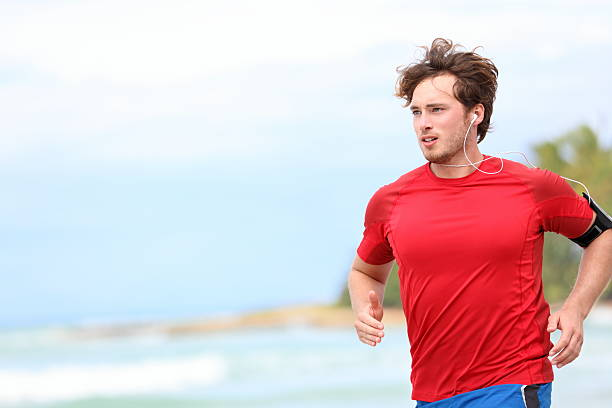 Man jogging Man jogging on beach. Male runner running listening to music on mp3 player or smart phone. Young caucasian male fitness sport model in red t-shirt. Click for more: red shirt stock pictures, royalty-free photos & images
