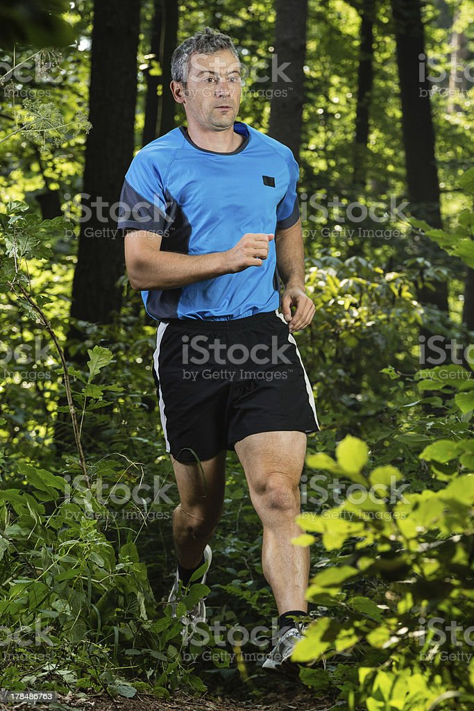 man jogging through the forest royalty-free stock photo