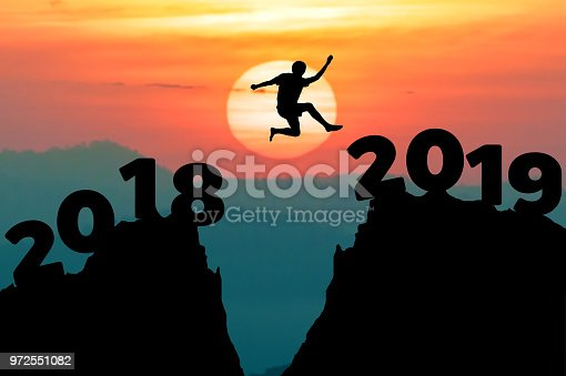 istock Man jump between 2018 and 2019 years. Happy new year 2019 concept for the achievement. 972551082