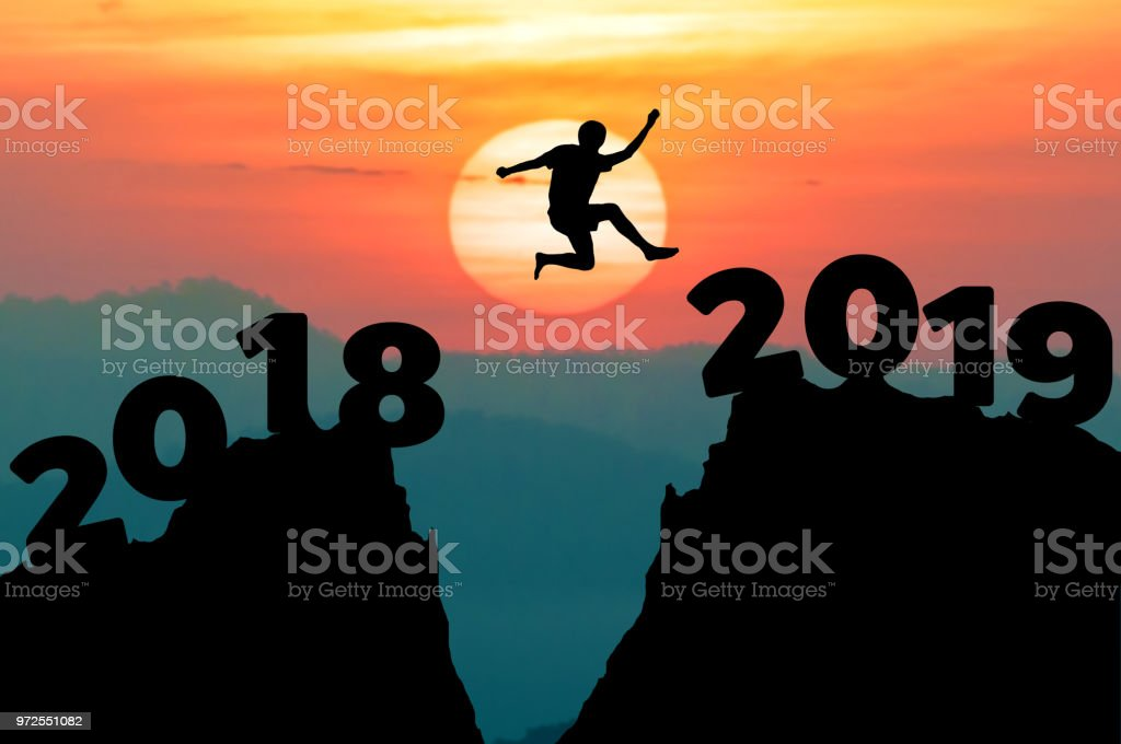 Man jump between 2018 and 2019 years. Happy new year 2019 concept for the achievement. stock photo